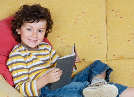 boy reading book on sofa