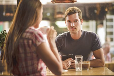 Photo for Young couple on first date drinking coffee, shot through glass - Royalty Free Image