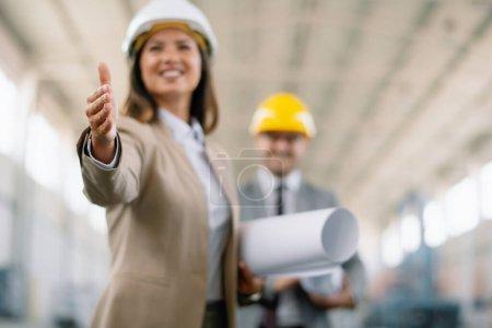 Photo pour Femme d'affaires souriante serrant la main avec un homme d'affaires sur fond. Beaux architectes en usine. - image libre de droit