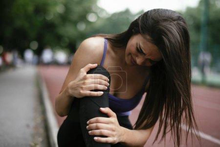 Knieverletzung. Frau hat Schmerzen im Knie nach Lauf im Freien.