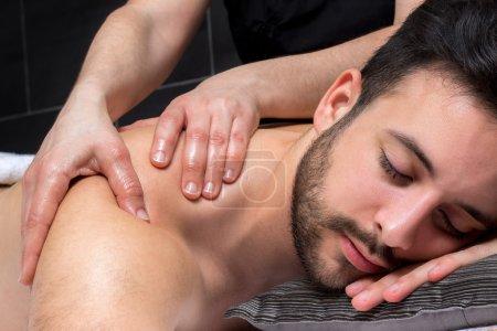 Shoulder massage on young man.