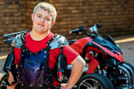Photo for Close up portrait of young handicapped sportsman standing in front of quad bike. - Royalty Free Image