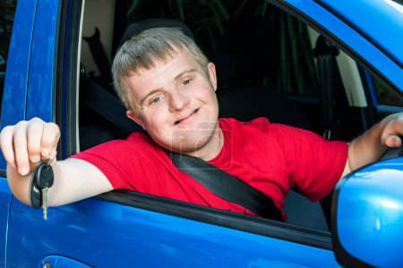 Photo for Close up portrait of young car driver with down syndrome showing car keys. Young man sitting behind steering wheel with safety belt fastened. - Royalty Free Image