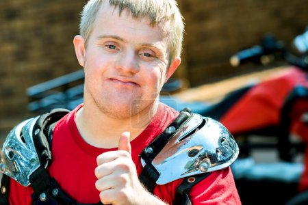 Photo for Close up portrait of young quad bike rider with down syndrome doing thumb up. - Royalty Free Image