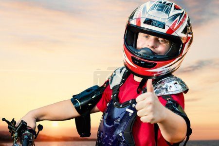 Photo for Close up portrait of young quad bike rider with down syndrome doing thumb up on bike. - Royalty Free Image