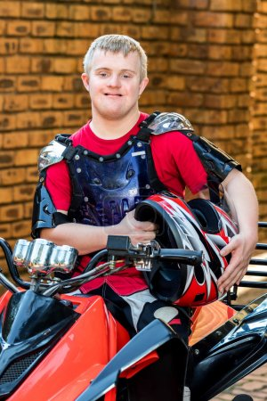 Photo for Close up portrait of young man with down syndrome sitting with sportswear and helmet on quad bike. - Royalty Free Image