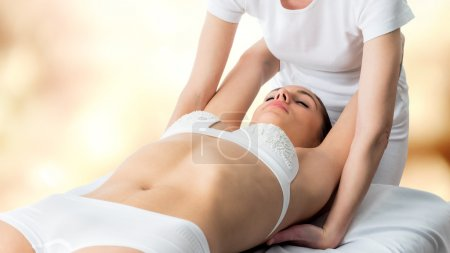 Osteopath stretching woman's shoulder blades.