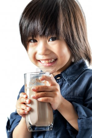 Cute asian youngster drinking chocolate milk.