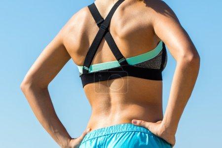 Female runner showing muscular back.