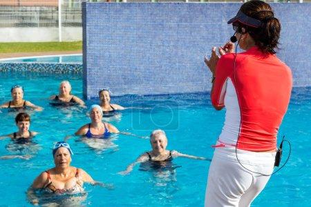 Aqua gym instructor doing senior class in pool.