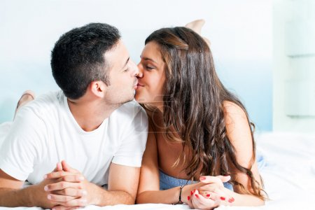 Young couple kissing in bedroom.