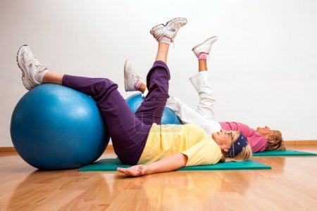 Photo for Two female seniors working out with fitness balls in health club. - Royalty Free Image