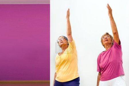 Senior women stretching in gym.