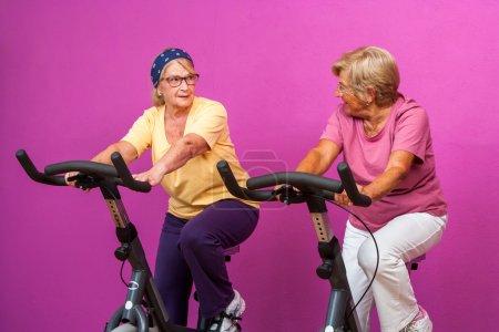 Photo pour Portrait de deux amies de fille seniors heureux travailler sur des vélos stationnaires dans la salle de gym. - image libre de droit