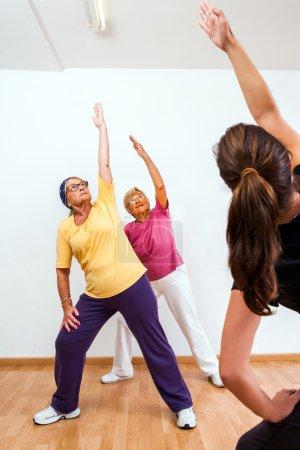 Personal trainer doing aerobic with senior ladies.