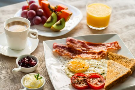 Photo pour Close up of english breakfast with fresh fruit and coffee. - image libre de droit