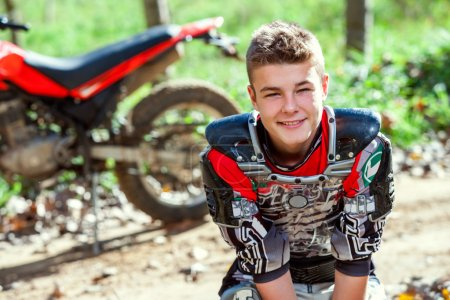 Photo for Close up portrait of attractive teen motocross rider outdoors with motorcycle in background. - Royalty Free Image