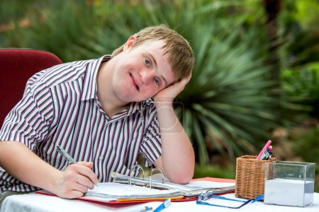 Photo for Close up portrait of Handicapped student resting on hand at desk in garden. - Royalty Free Image
