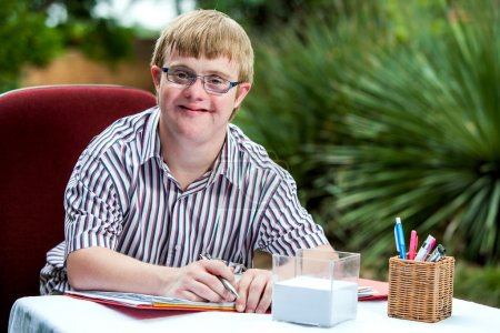 Photo for Close up portrait of handicapped student wearing glasses at desk in garden. - Royalty Free Image