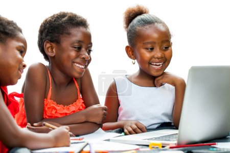 Three African kids laughing at scene on laptop.