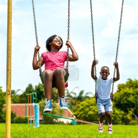 African kids having fun swinging in park.
