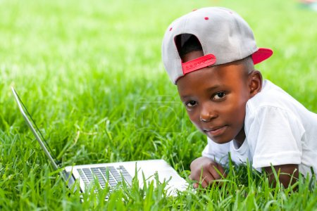 African boy laying with laptop on grass.