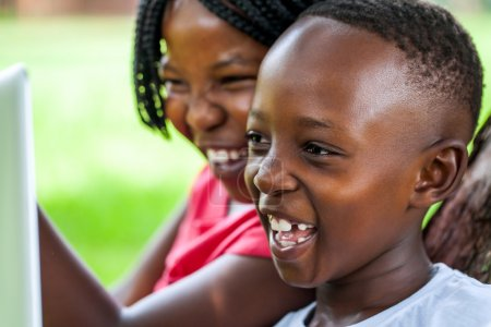 Laughing African kids looking at laptop screen.