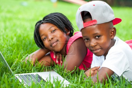 African kids laying on grass with laptop.