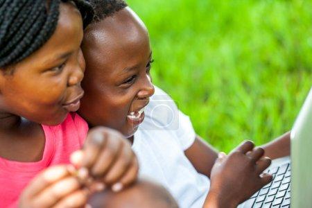 African kids having fun on laptop outdoors.