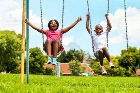 Photo pour Action portrait of shouting African kids playing on swing in neighborhood.Out of focus houses in background. - image libre de droit