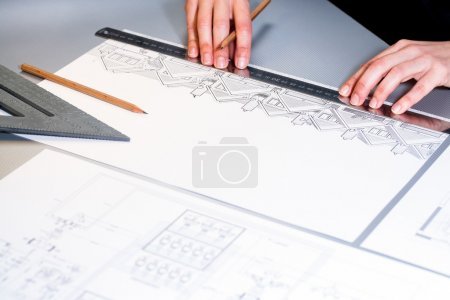 Hands measuring detail on house plans.