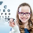Close up portrait of young girl holding glasses wi...