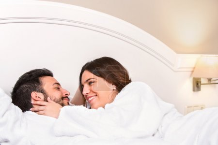 Photo pour Gros plan portrait de mignon jeune couple en peignoir. Couché sur le lit dans la chambre d'hôtel. Fille montrant l'affection . - image libre de droit