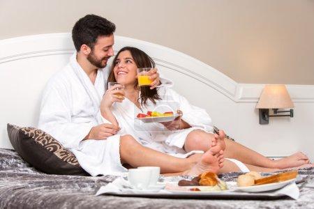Photo pour Gros plan portrait de jeune couple en lune de miel dans la chambre d'hôtel. Couple bénéficiant d'un service en chambre avec plateau petit déjeuner . - image libre de droit