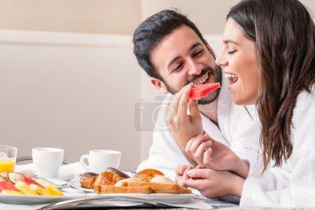 Photo pour Gros plan portrait amusant de couple en peignoir sur lit profitant du petit déjeuner ensemble . - image libre de droit