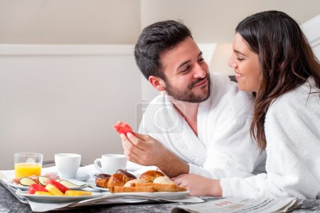 Photo for Close up portrait of young attractive couple enjoying breakfast in hotel room. - Royalty Free Image