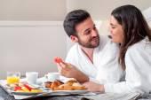 Couple enjoying hotel room service.