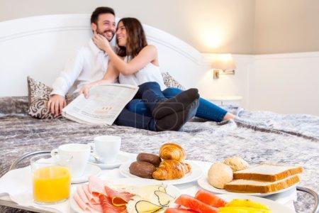 Photo pour Détail rapproché du plateau de petit déjeuner sur le lit avec jeune couple riant en arrière-plan . - image libre de droit