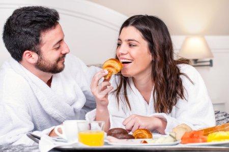 Photo pour Gros plan portrait de couple s'amusant au petit déjeuner dans la chambre d'hôtel.Fille sur le point de prendre morsure de croissant . - image libre de droit