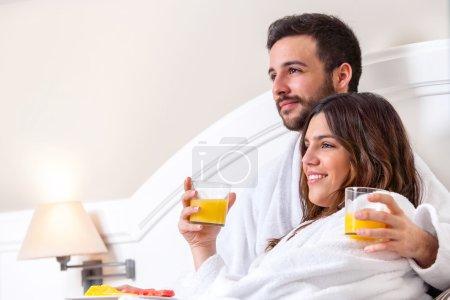 Photo pour Gros plan portrait de couple en peignoir sur lit buvant du jus d'orange . - image libre de droit