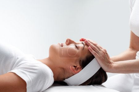 Woman relaxing at reiki session.