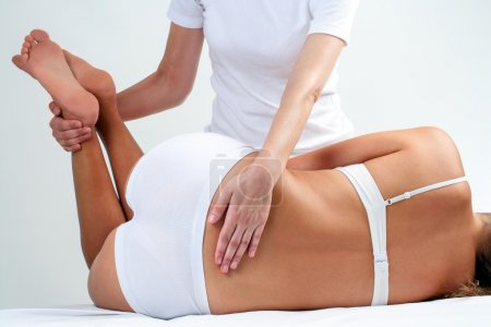 Photo for Therapist doing lower back massage on woman - Royalty Free Image