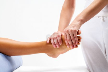 Physiotherapist doing reflexology massage