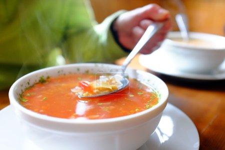 Photo pour Macro gros main tenant la cuillère avec un bol chaud de la soupe. Cuillère avec hot steamy bol de soupe aux légume. - image libre de droit