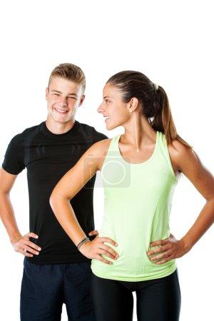 Foto de Primer plano retrato de atractiva pareja adolescente en ropa deportiva listo para el entrenamiento de fitness aislado sobre fondo blanco - Imagen libre de derechos