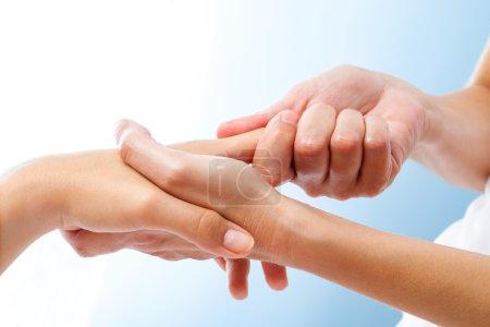 Therapist manipulating female hand