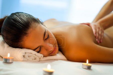 Photo for Close up portrait of attractive young woman having relaxing body spa treatment in dim candle light. Therapist in background massaging back - Royalty Free Image