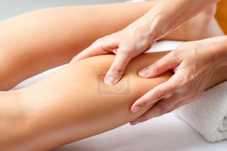 Hands applying pressure with fingers on calf muscle.