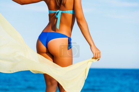 Attractive female suntanned body on beach.