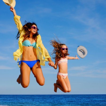 Young girls on holiday jumping with hats.